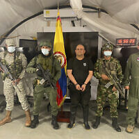 """In this photo released by the Colombian presidential press office, one of the country's most wanted drug traffickers, Dairo Antonio Usuga, alias """"Otoniel,"""" leader of the violent Clan del Golfo cartel, is presented to the media at a military base in Necocli, Colombia, October 23, 2021. (Colombian presidential press office via AP)"""