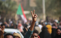 Pro-democracy protesters flash the victory sign as they take to the streets to condemn a takeover by military officials, in Khartoum, Sudan, October 25, 2021. (Ashraf Idris/AP)