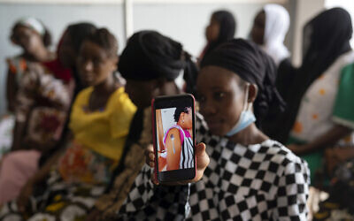 Oumie Nyassi shows a video circulating online and that has been debunked of a woman claiming she was magnetized after receiving the COVID-19 vaccine, in a doctor's office at Serrekunda, Gambia hospital on Sept. 23, 2021. (AP Photo/Leo Correa)