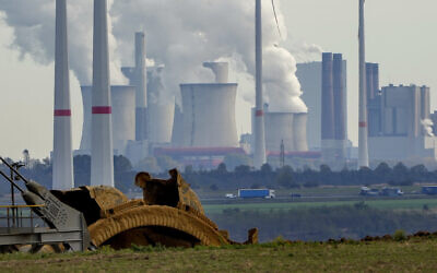 Steam comes out of the chimneys of the coal-fired power station Neurath near the Garzweiler open-cast coal mine in Luetzerath, Germany, Monday, Oct. 25, 2021. (AP Photo/Michael Probst)