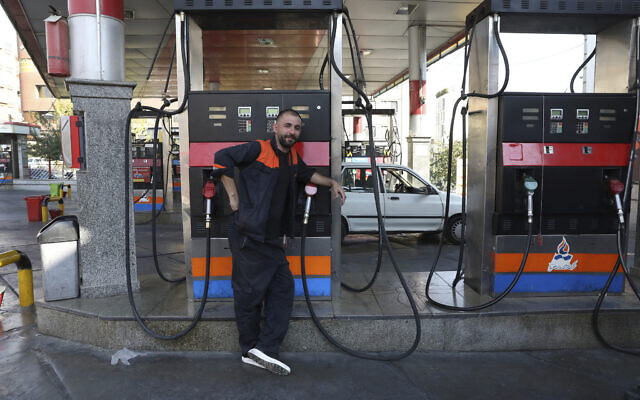 A worker leans against a gasoline pump that has been turned off, at a gas station in Tehran, Iran, Tuesday, Oct. 26, 2021. (AP Photo/Vahid Salemi)
