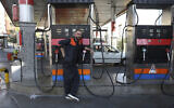 A worker leans against a gasoline pump that has been turned off, at a gas station in Tehran, Iran, October 26, 2021. (AP Photo/Vahid Salemi)