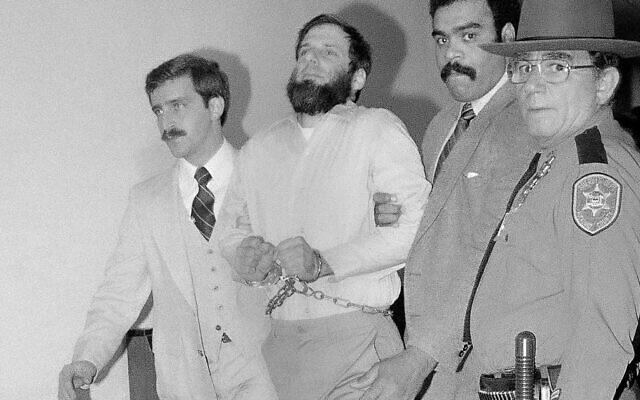 In this Nov. 23, 1981, file photo, law officials escort a handcuffed David Gilbert, second from left, from Rockland County Court in New City, N.Y. (AP/David Handschuh)