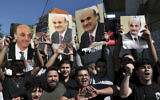 Supporters of Samir Geagea, the leader of the Christian Lebanese Forces party, chant slogans as they hold his photo after he declined to show up for questioning over deadly clashes in Beirut earlier this month, outside his residence in Maarab, east of Beirut, Lebanon, October 27, 2021. (Bilal Hussein/AP)