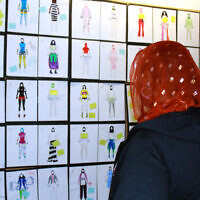 Illustrative: In this June 10, 2015 photo, a girls looks at design drawings for Muslim girls' athletic wear before a fashion show in Minneapolis. (AP/Jeff Baenen)