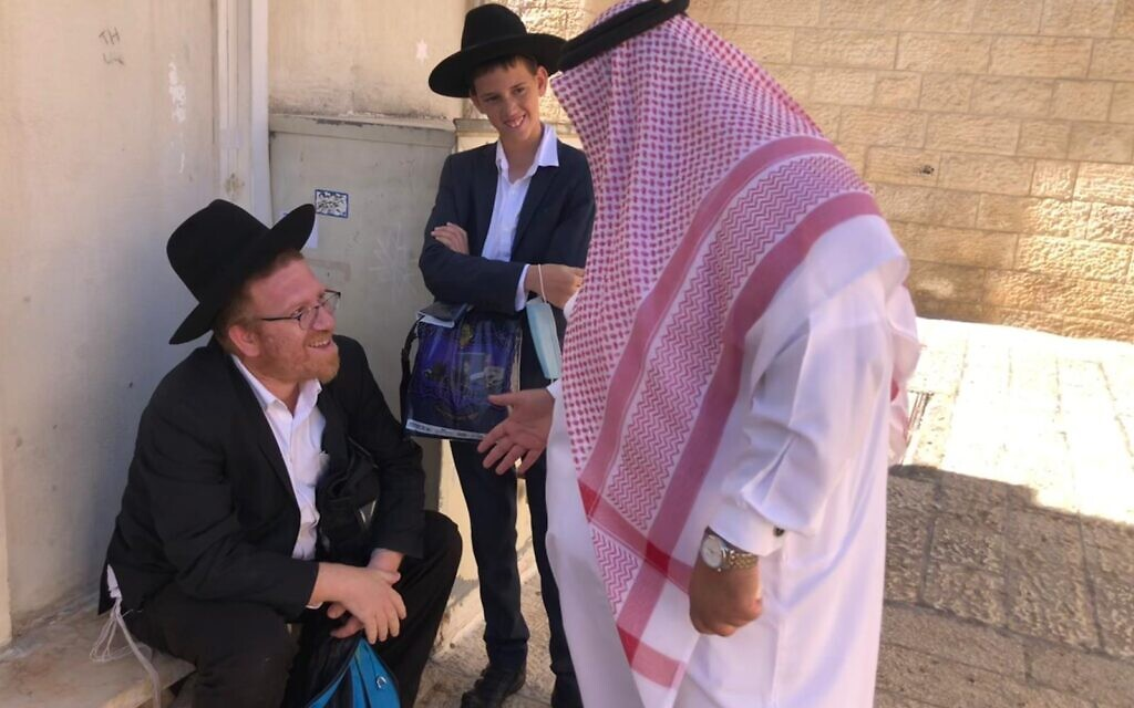 Bahraini education official Mohammed Saleh speaks to a Haredi father and son in the Old City of Jerusalem, October 6, 2021 (Lazar Berman, Times of Israel)