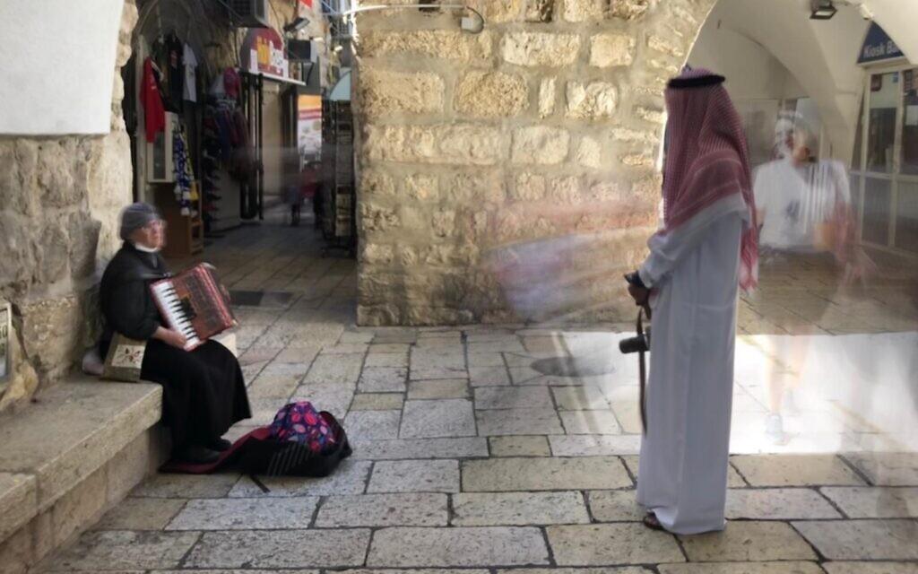 Bahraini activist Mohammed Al Shaer listens to a street musician in Jerusalem's Jewish Quarter, October 6, 2021 (Lazar Berman, Times of Israel)