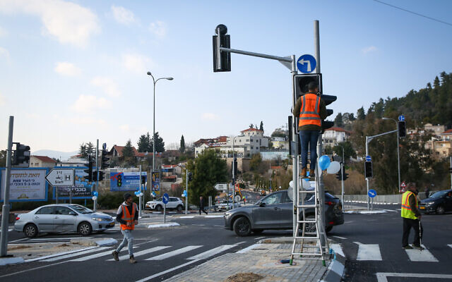 Illustrative: Workers operate a traffic light in the northern Israeli city of Tzfat, January 14, 2020. (David Cohen/Flash90)