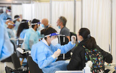 Medical technicians test passengers for COVID-19 at Ben Gurion International Airport, on March 8, 2021. (Flash90)