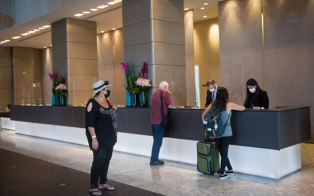 Guests at the reception desk in a Tel Aviv hotel, April 27, 2021. (Miriam Alster/ FLASH90)