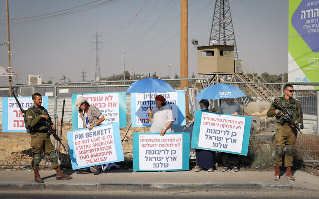 Israelis protest at the Gush Etzion junction against Prime Minister Naftali Bennett's visit to US president Joe Biden and on what they claim to be the freeze on settlement development, on August 24, 2021. (Gershon Elinson/Flash90)