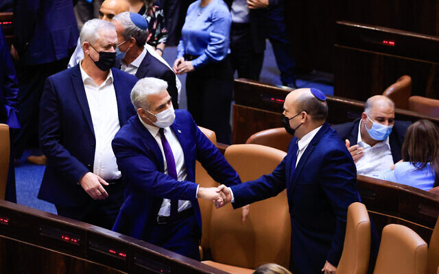 Prime Minister Naftali Bennett (right) shakes hands with Foreign Minister Yair Lapid during a plenum session and a vote on the state budget at the Knesset plenum in Jerusalem, September 2, 2021. (Olivier Fitoussi/Flash90)