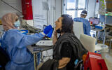 A healthcare worker takes a swab sample from a woman for COVID-19, after returning from overseas at the Ben Gurion International Airport on September 20, 2021. (Nati Shohat/Flash90)