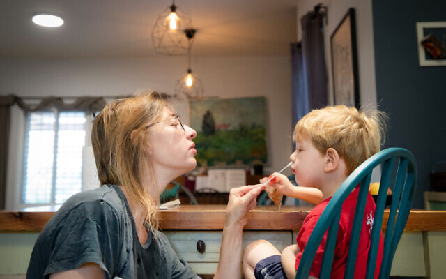 A mother tests her son with a COVID-19 rapid antigen home test in Haniel, central Israel on September 27, 2021. (Chen Leopold/Flash90)