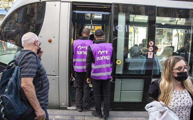 Police and light rail inspectors enforce coronavirus regulations on public transportation, on October 3, 2021,  in Jerusalem. (Olivier Fitoussi/Flash90)