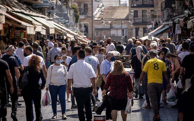 Israelis, some wearing face masks, shop at the Mahane Yehuda market in Jerusalem on October 5, 2021. (Yonatan Sindel/Flash90)