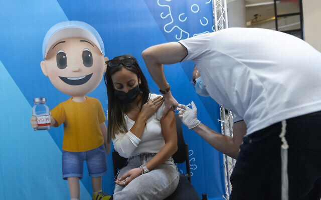 People receive a dose of the COVID-19 vaccine at a health clinic, in Jerusalem, on October 7, 2021. (Olivier Fitoussi/Flash90)