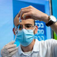 A medic prepares a dose of the COVID-19 vaccine on October 7, 2021, in Jerusalem.  (Olivier Fitoussi/Flash90)