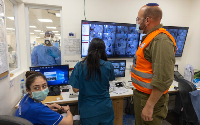 Shaare Zedek hospital staff and an IDF soldier gathered around computer screens on October 14, 2021. (Olivier Fitoussi/Flash90)