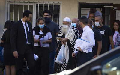 One of the men arrested on suspicion of murdering Avraham Edri and Nissim Shitrit is brought for a court hearing outside the Jerusalem Magistrate's Court on October 17, 2021. (Olivier Fitoussil/Flash90)