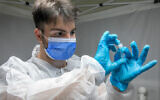 A worker takes a COVID-19 rapid antigen test in Lod, Israel, on October 17, 2021. (Yossi Aloni/Flash90)