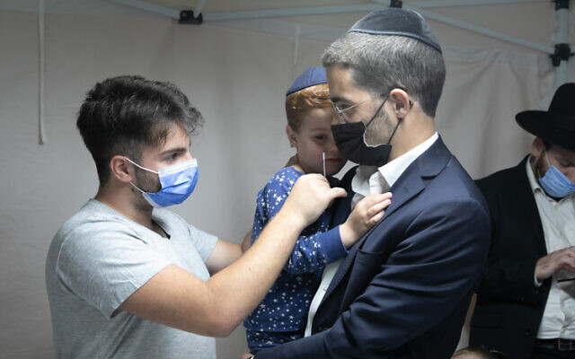 An ultra-Orthodox man has his son tested for COVID-19 in in Lod, on October 17, 2021. (Yossi Aloni/Flash90)