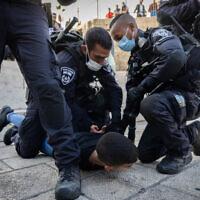 Police arrest a Palestinian youth outside Damascus Gate near Jerusalem's Old City, on October 20, 2021. (Yonatan Sindel/Flash90)