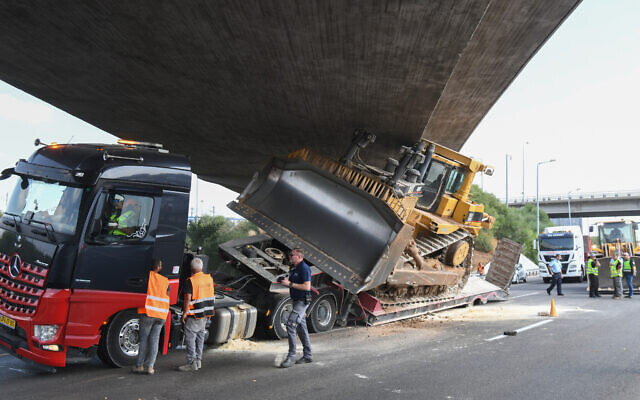 Police at the scene where a truck transporting a bulldozer hit a bridge on October 26, 2021 (Flash90)
