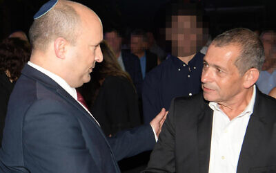 Prime Minister Naftali Bennett (L) greets outgoing Shin Bet head Nadav Argaman  at an event to honor the departing security chief on October 14, 2021 (Amos Ben Gershom/GPO)