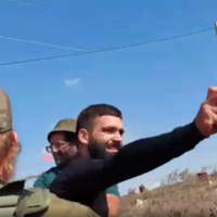 Screen capture from video of a man pepper-spraying volunteers helping Palestinian olive farmers, October 25, 2021. (Rabbis for Human Rights)
