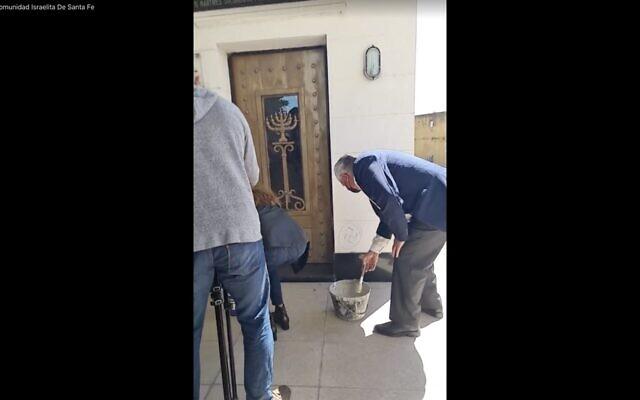 Volunteers paint over swastikas in a Jewish cemetery in Santa Fe, Argentina. (Screenshot from Facebook livestream via JTA)