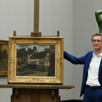 German art historian and gallery director Ralph Gleis stands next to a Pissarro painting that was looted by the Nazis, on October 18, 2021. (CHRISTOF STACHE /AFP)