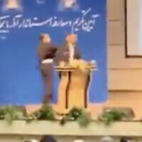 In this screen capture from video aired by Iranian state television on October 23, 2021, an unidentified mans slaps Eastern Azerbaijan Governor Abedin Khorram as he speaks in the provincial capital Tabriz. (Screenshot/Twitter)