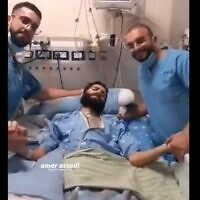 Two Arab Israeli nurses at Kaplan hospital pose with Miqdad Qawasmeh, a Hamas member who is on a hunger strike to protest being held in administrative detention (Screen capture/ Kan)