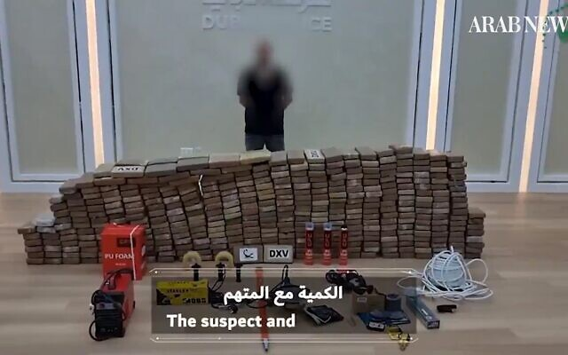 A suspect in a major drug bust in the United Arab Emirates is photographed alongside the haul by police -- some 500 kilograms of cocaine -- on October 10, 2021 (screenshot: Arab News)