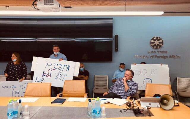 Foreign Ministry employees disrupt a meeting of the promotions committee as a committee member waits for them to leave, October 19, 2021 (Lazar Berman/Times of Israel)