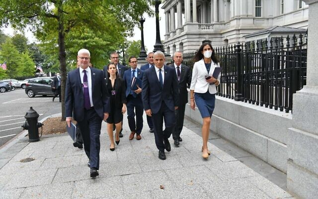 Foreign Minister Yair Lapid walks with his aides in Washington on October 12, 2021. (Shlomi Amsalem/GPO)