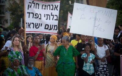 Members of the Hebrew Israelites Community of the southern city of Dimona protest against deportation orders given to some of their members, Habima Square, Tel Aviv, June 1, 2021. Th banner says, 'We are an integral part of the People of Israel.'  (Miriam Alster/Flash90)