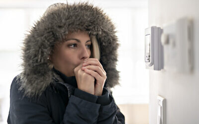 A woman feeling the cold inside a house. (LSOphoto via iStock by Getty Images)