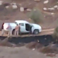 Israeli settlers are seen surronding an IDF vehicle near the settlement of Adei Ad, October 13, 2021. (Video screenshot/courtesy)