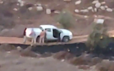 Israeli settlers are seen surrounding an IDF vehicle near the settlement of Adei Ad, October 13, 2021. (Video screenshot/courtesy)